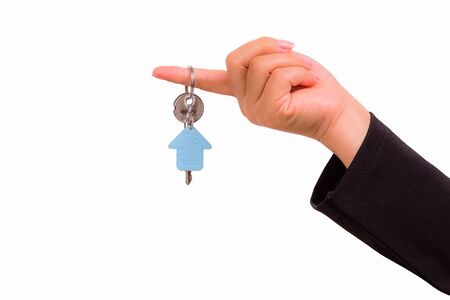passkey: Hand of woman with a keychain in the shape of the house isolated on white background