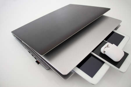 laptop, notebook, tablet, phone and headphones intertwined and grift on a white background. communication devices,