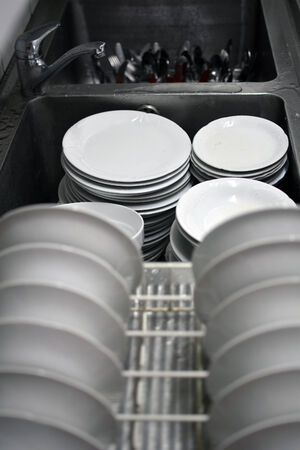Resturant dirty dishes awaiting cleaning process. photo