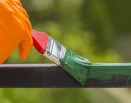 iron fence: Hand wearing orange gloves and painting with a paint brush. Stock Photo