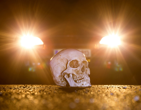 placed: Skull placed on the ground, infront of a car.