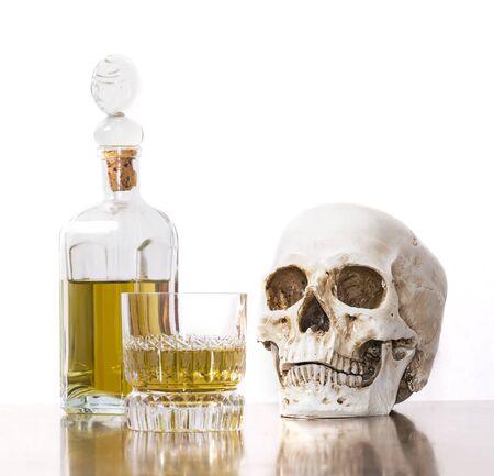 adult bones: Human skull with alcohol bottle. Stock Photo