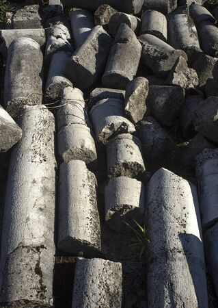man made object: Old pillars laying on the ground, damaged