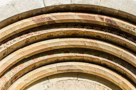 man made object: Many arches over an an old church entrance.