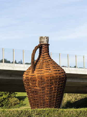 wine road: Big bottle for wine, placed near a road.. Stock Photo