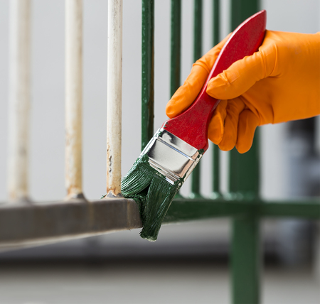 Hand wearing orange gloves and painting with a paint brush. Stock Photo