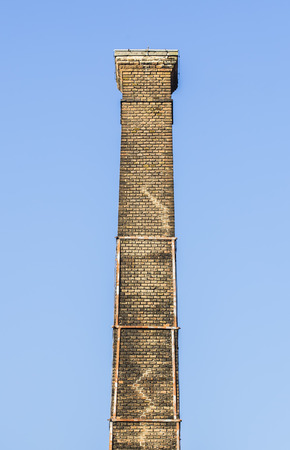 photorealism: Very old brick chimney with clear sky.