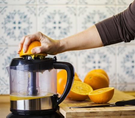 squeezing: Squeezing orange to extract some healthy juice. Stock Photo