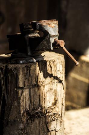 holdfast: Metalworking hand tool on a tree stump. Stock Photo