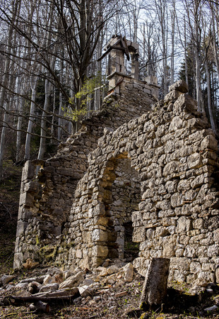 man made structure: Old rock wall falling apart with church structure. Stock Photo