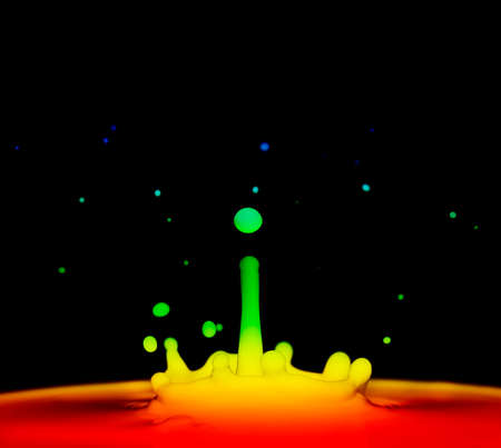 pictured: Splash of colored liquid, pictured on a black background.