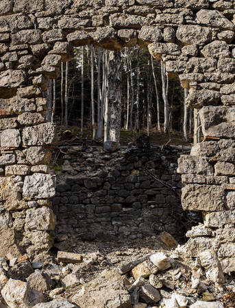 man made structure: Demolished rock wall with an arch.