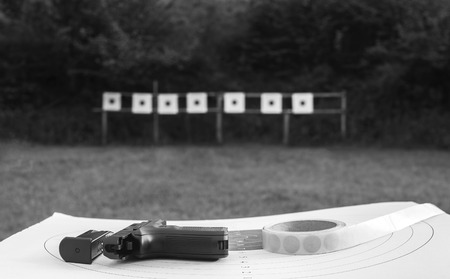 casing paper: Gun placed on a used target, with more blurred  targets in the background. Stock Photo
