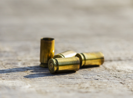 placed: Empty bullet shells placed on a wooden table. Stock Photo