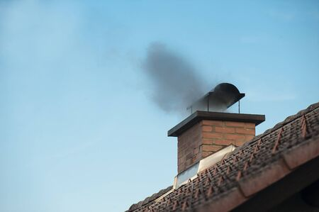 Chimney with a smoke coming out. Stock Photo