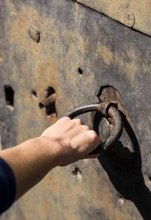 closed fist: Holding old door metal ring with a hand.