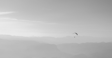 Gliding in the air above mountains with a parachute. Stok Fotoğraf