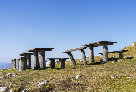 Wooden benches on top of a hill with a clear sky and mountain view.