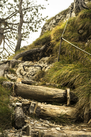 Improvised mountain staircase with a metal rope for holding on.