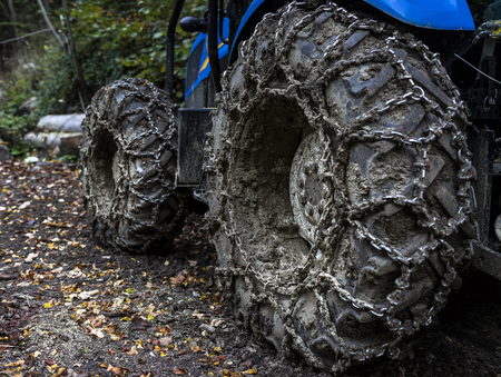 heavy tractor with chains for heavy work in the woods. Stok Fotoğraf