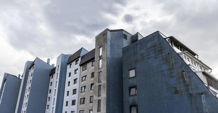 Small urban skyscraper shaped in unusual way slightly leaned. Stok Fotoğraf