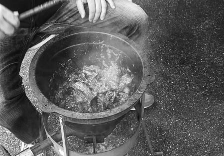 Person is cooking some goulash in a big metal pan with gas heater.