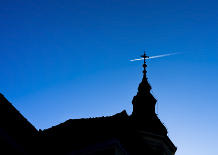 Airplane flying above christian church silhouette.