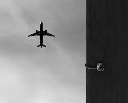 Security camera mounted on a wall with a plane above. Stok Fotoğraf