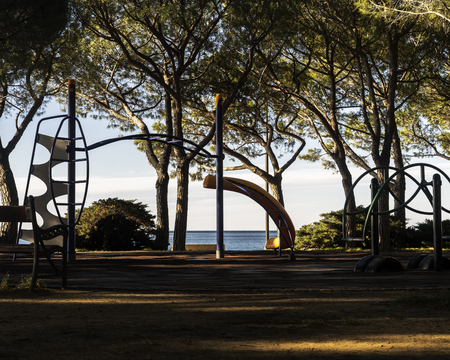 Small park with playground near a mediterranean sea. Stok Fotoğraf - 120368554