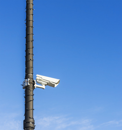 Surveillance camera with christmass lights wrapped around the pole. Stok Fotoğraf - 120368567
