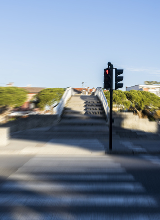 Blurred pedestrian cross with red semaphore.