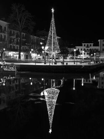Grado, Italy, EU - January 2, 2019: Small christmass tree near a mediterranean sea canal.