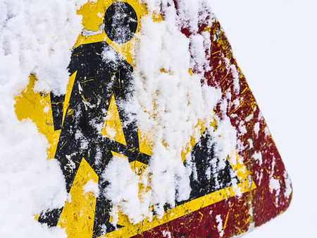 Road works sign covered with snow in winter time.