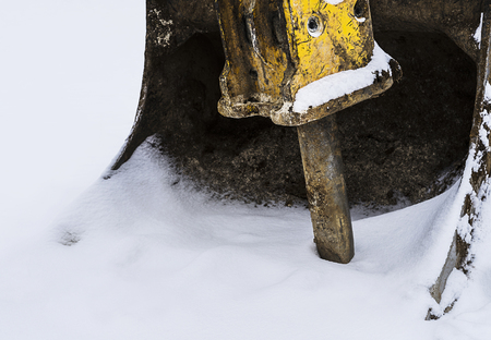 Small excavator part covered with some snow in winter.