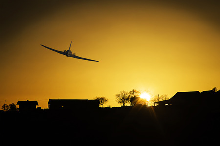 Sunset with a plane  flying by and silhouette of houses.