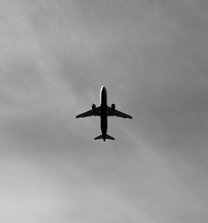 Commercial aircraft is flying high above, and on its way to its destination. Stok Fotoğraf