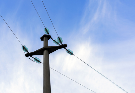Concrete electric pole with insulator discs and bright sky.