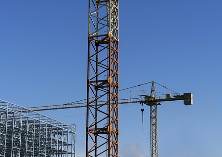 Two construction cranes with a clear sky behind of them.