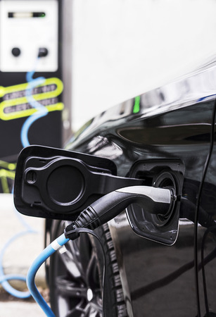 Electric cable is providing energy for charging electric car at the station. Stok Fotoğraf