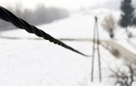 Electric cable is leading towards the wooden pole providing electricity. Stok Fotoğraf - 120368960