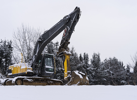 Excavator machine covered with snow in winter