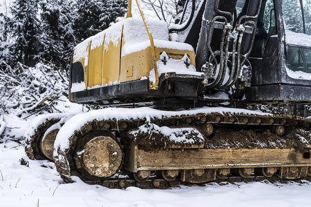 Excavator machine covered with some snow in winter.