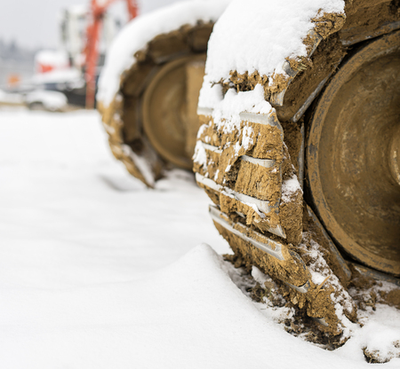 Heavy excavator steel tracks covered with snow