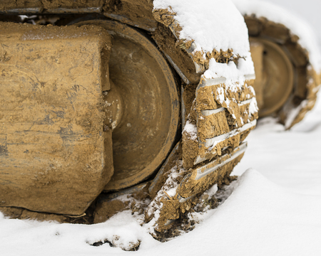 Heavy excavator steel tracks covered with some snow in winter time. Stok Fotoğraf - 120369005