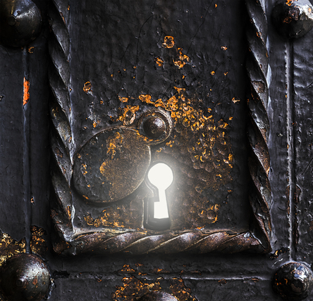 Old metal keylock with a bright light shining out. Stok Fotoğraf