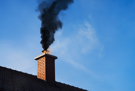 Chimney on fire with a black smoke coming out. Archivio Fotografico