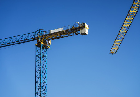 Two construction cranes with a clear sky behind of them. Stok Fotoğraf - 120369021