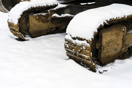 Heavy excavator steel tracks covered with some snow in winter time.
