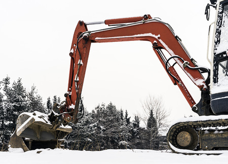 Small excavator machine covered with some snow in winter time.