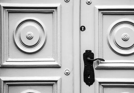 Older type of door with circular shapes and a metal door handle.